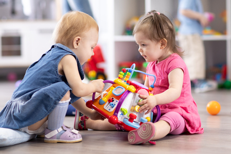 Babies conflict in nursery. Child is trying to take away toy from another kid.