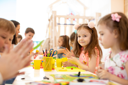 kindergarten kids doing arts and crafts with teacher in day care centre