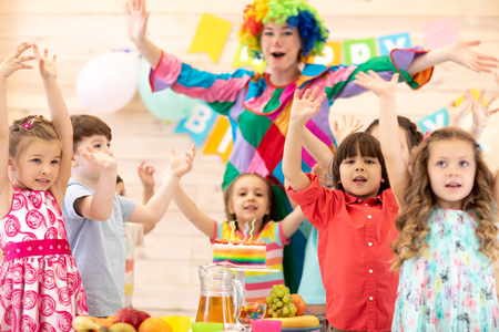 Clown playing with children. Kids group celebrate birthday and pose for camera standing at table. Holiday in a childrens club.