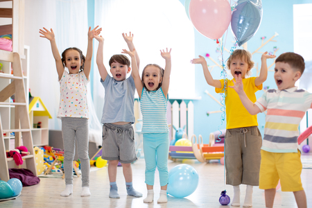 Group of emotional friends with their hands raised. Kids have fun pastime in daycare