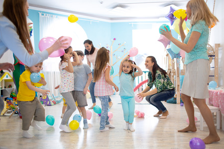 joyful kids and their parents entertain and have fun with color balloon on birthday party Banco de Imagens