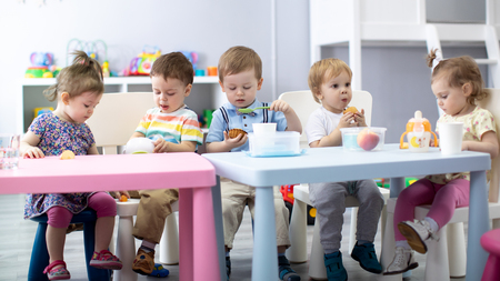 Nursery babies eating food. Kids have lunch in daycare