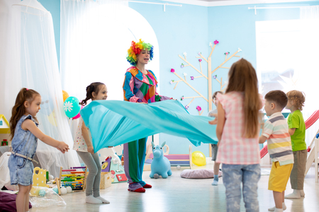 Children group have fun on party. Clown entertains kids