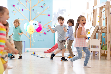 childhood, leisure and people concept - group of happy kids playing tag game and running in spacious room Banco de Imagens