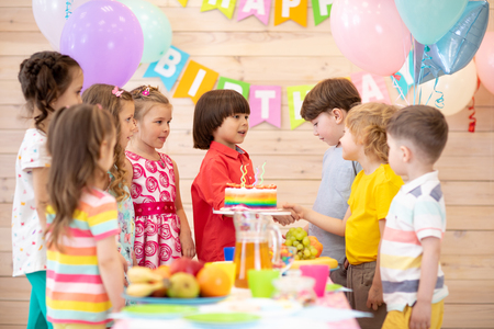 Groups of children come to party and shake hands with a birthday boy. Cheerful pretty kids have come to congratulate their friend Banco de Imagens