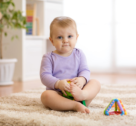 Lindo bebé gracioso sentado en una alfombra en casa