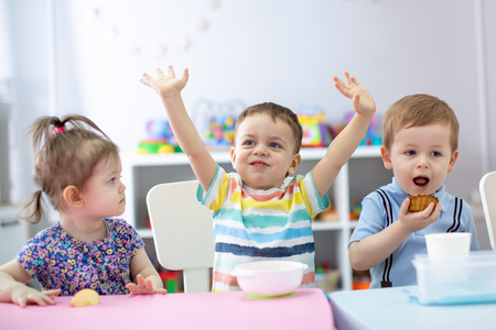 Group of happy kids have a lunch in kindergarten