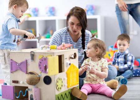 Niños jugando con juguetes educativos en la guardería.