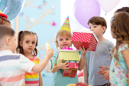 Group of diversity children party together. Kids giving gift boxes to boy during birthday party in daycare or club