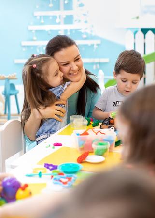 Teacher with kids working with plasticine at kindergarten or playschool Banco de Imagens