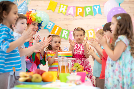 Children with clown clown clap around table with birthday cake
