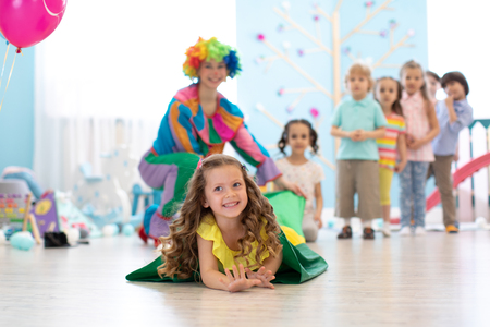 Happy children playing in childrens playroom for birthday party or entertainment centre. Kids amusement park and play center indoor.