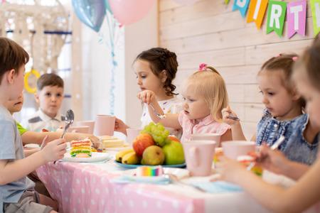 children eat cake at birthday party