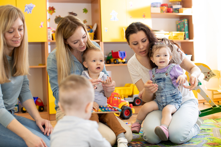 Babies with their mothers play with toys in nursery