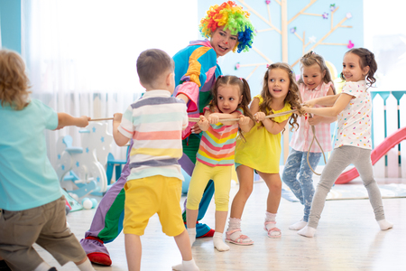 Excited kids playing tug-of-war in club