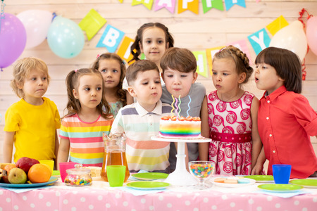 Kids celebrate birthday party and blow candles on festive cake Banco de Imagens