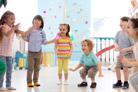 Group of happy children jump indoor. Kids play together Banco de Imagens