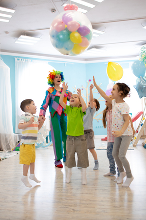 holidays, childhood and celebration concept - several kids having fun and jumping on birthday party in entertainment centre Banco de Imagens