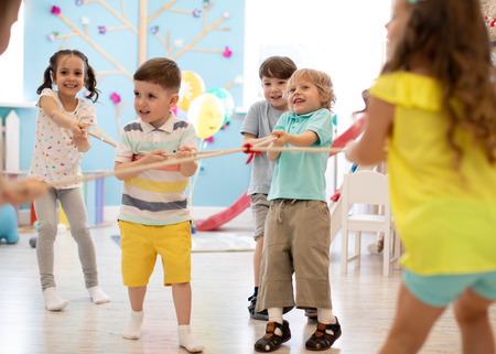 Excited kids playing tug of war in club