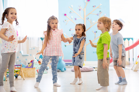Happy children having fun dancing indoor in a sunny room at daycare or entertainment center