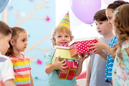 Joyful little kid boy receiving gifts at birthday party. Holidays, birthday concept.
