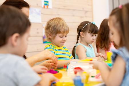 Group of kids on art classes with teacher in kindergarten