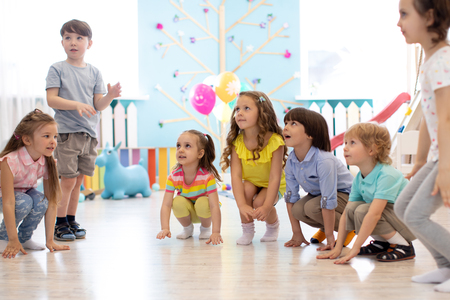 Preschool kids boys and girls squat playing in kindergarten