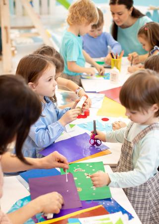 Desarrollo de aprendizaje de niños en edad preescolar. Proyecto infantil en jardín de infantes. Grupo de niños y maestros cortando papel y pegando con pegamento en barra en la clase de arte en el jardín de infantes o guardería Foto de archivo