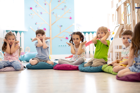 Kids seating on floor and show gestures making task