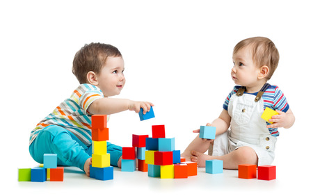 Two kids building block towers. Isolated on white background