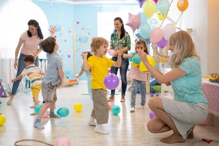los niños alegres y sus padres se entretienen y se divierten con globos de colores en la fiesta de cumpleaños Foto de archivo