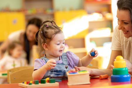 Babies with teachers play with developmental toys in nursery