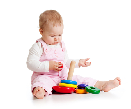 Adorable baby playing enthusiastically woth educational toy. Small kid sits on floor, isolated on white
