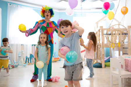 joyful kids and clown play with color balloon on birthday party
