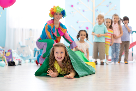 Children play with clown on birthday party in entertainment centre Banco de Imagens