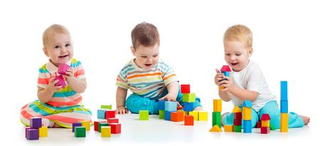 Lindos bebés niños pequeños jugando con juguetes o bloques y divirtiéndose mientras están sentados en el piso aislado sobre fondo blanco. Foto de archivo