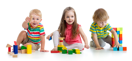 Lindos niños pequeños jugando con juguetes o bloques y divirtiéndose mientras están sentados en el piso aislado sobre fondo blanco.