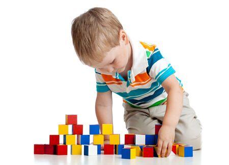 Niño pequeño jugando juguetes de bloques de madera aislado en blanco