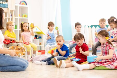 Group of kindergarten children play with musical toys. Early musical education in daycare