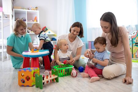 adorable toddlers playing with colorful toys and mothers in nursery room. Nursery babies playing with adults in day care center