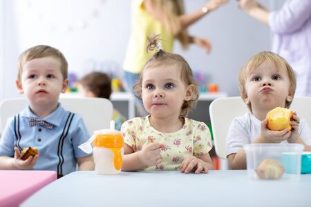 Nursery babies have a dinner in kindergarten. Little boys and girls sitting at the table with lunch and eat appetizing. Children with caregiver in daycare centre Archivio Fotografico - 130445946
