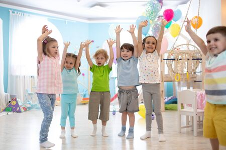 Happy kids with hands up at daycare Stock Photo