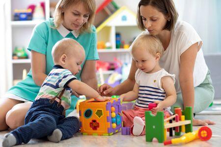 Babys, die zusammen mit Müttern im Klassenzimmer im Kindergarten oder in der Vorschule spielen Standard-Bild