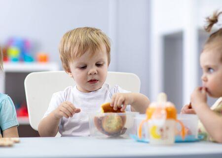 Baby have a lunch in kindergarten Archivio Fotografico
