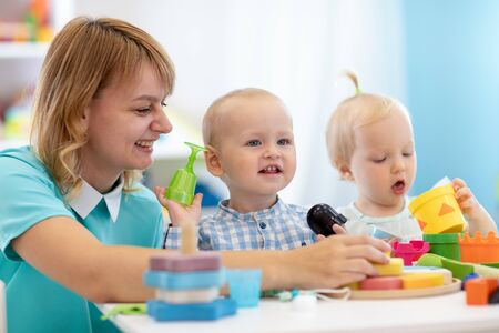 Kindergarten babies together with teacher playeducational toys at sunny day in nursery