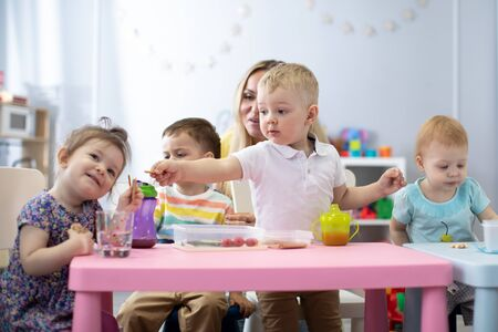 Kids have a dinner in kindergarten. Little boys and girls from the group of children sitting at the table with lunch and eat appetizing. Children with caregiver in day care centre Stock Photo
