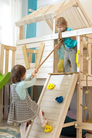 kid boy helps child girl climb the rope up in playroom Reklamní fotografie