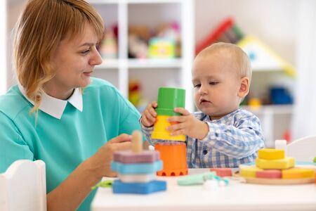 Dziecko z matką w przedszkolu w domu. Dziecko z nauczycielem bawiące się edukacyjnymi zabawkami z kubkiem w przedszkolu lub żłobku Zdjęcie Seryjne