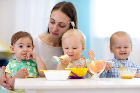 Group of nursery babies eat healthy food with kindergartener help. Lunch break in creche. Little children have dinner in daycare