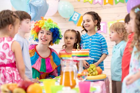 Clown playing with children. Kids group celebrate birthday at table. Holiday in a childrens club. Stock fotó